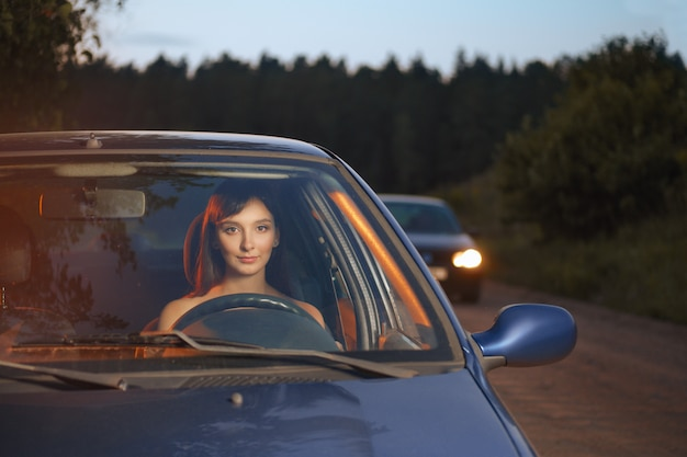Woman driving the car in the evening