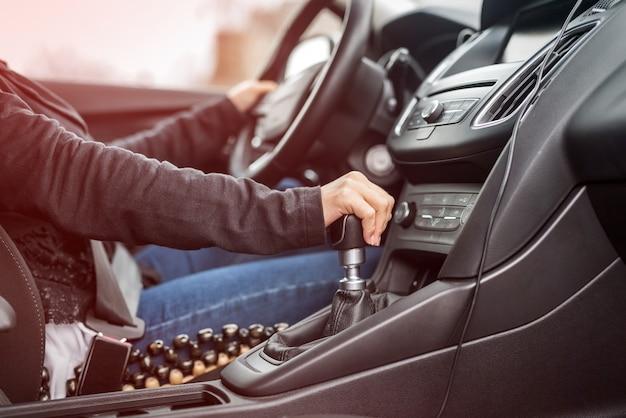 車を運転している女性、ハンドルのクローズアップを手に