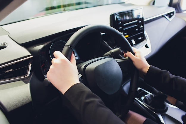 Woman driving a car, hands on steering wheel close-up.