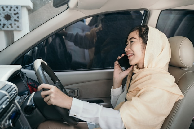 Woman driving car while having phone call