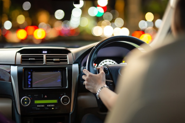 Woman driving a car with bokeh lights from traffic jam at night time.