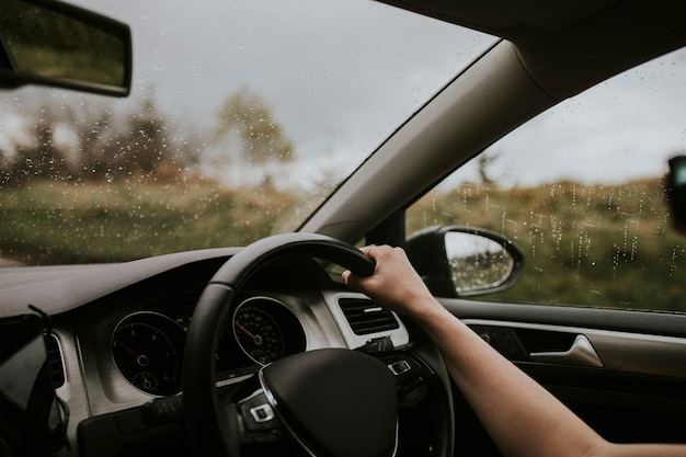 Woman driving a car with hand on the steering wheel