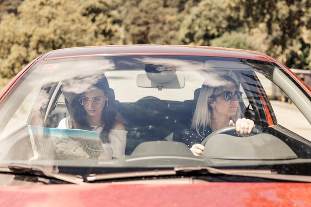 Woman driving the car with her female friend looking at map