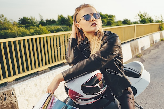 Woman driving on motorbike wearing fashionable sunglasses