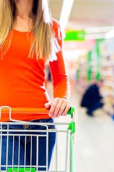 スーパーマーケットで食料品の買い物をしながらショッピングカートを運転する女性
