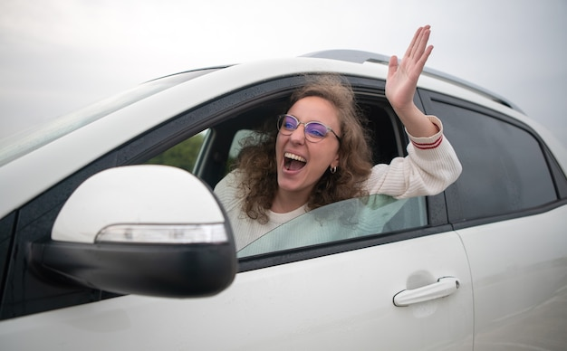 Woman driving very angry sticking her arm out the window in a traffic jam