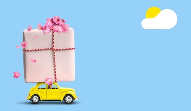 Женщина за рулем желтый ретро автомобиль с подарочной коробкой на крыше с цветами на синем фоне.