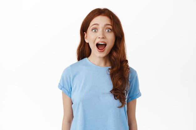 女性はあごを落とし、カメラをじっと見つめ、素晴らしいニュースを聞き、何かクールなものに驚いて、白の上に立っています。