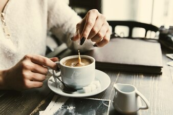 Woman drops sugar in a cup of coffee