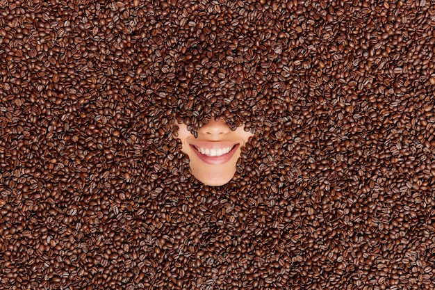 Woman drowned in coffee beans smiles broadly shows teeth going to prepare her favorite beverage