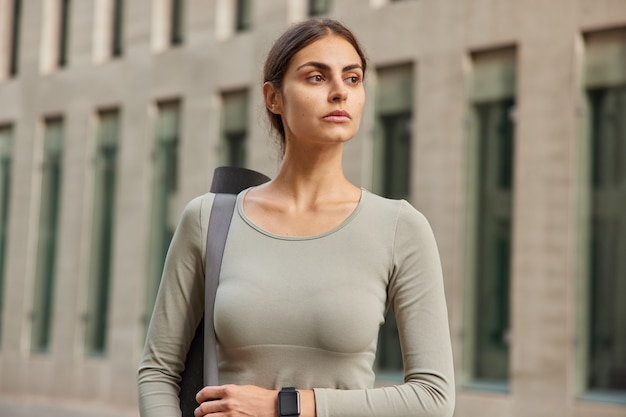 Woman drssed in sportswear carries karemat on shoulder wears smartwatch looks into distannce stands near building rests after physical activity
