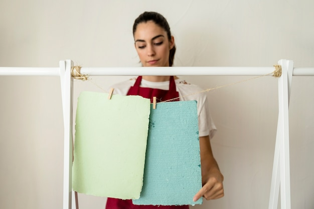 Woman drying papers with clothespin on string