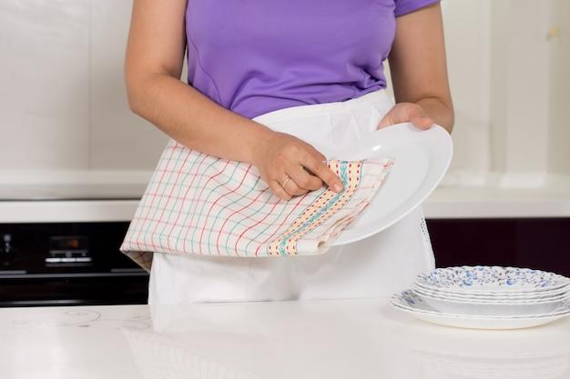 台所で皿を乾かす女性