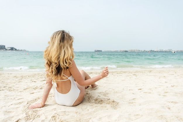 Woman at dubai beach wearing white swimsuits