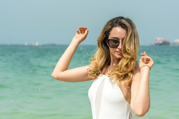 Woman at dubai beach in white swimsuits