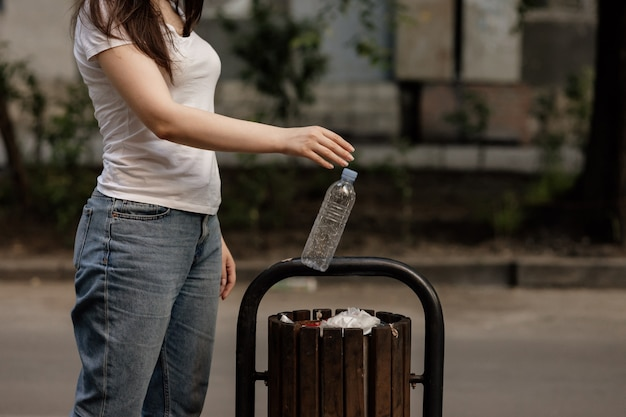 A woman dump a plastic bottle  to wooden recycle bin in a park. waste recycling