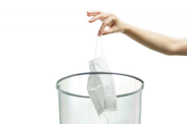 使用済みの医療用フェイスマスクをゴミ箱、コロナウイルス、またはcovid-19保護に捨てた女性。