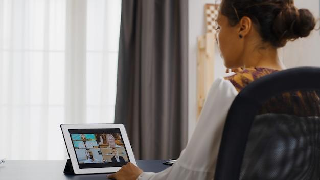 Женщина во время видеоконференции с коллегами, работая из домашнего офиса.