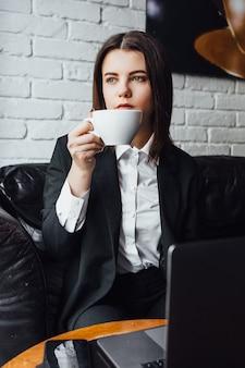 コーヒーとラップトップを持ってカフェに座っている休憩中の女性!ライフスタイル!
