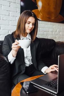 コーヒーとラップトップを持ってカフェに座っている休憩中の女性!