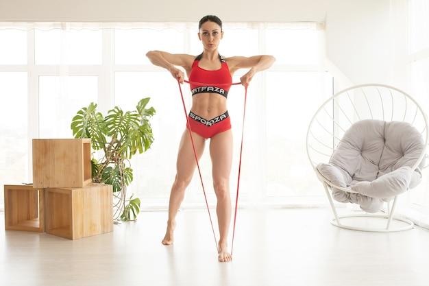 Женщина во время фитнес-тренировки дома с резиновой лентой сопротивления