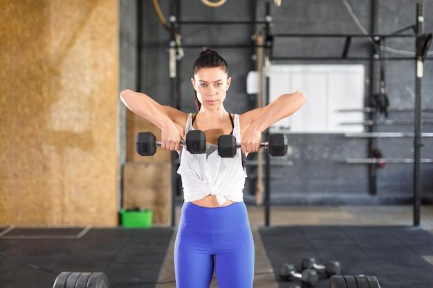 체육관에서 훈련하는 동안 그녀는 덤벨 운동을 전면에서 봅니다.