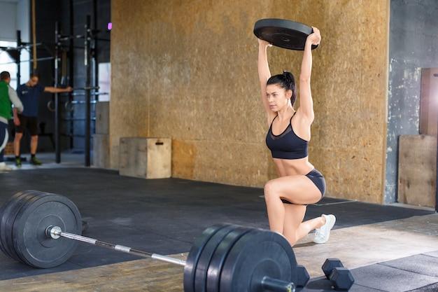 체육관에서 훈련하는 동안 여자는 돌진하고 머리 위로 체중을 유지합니다