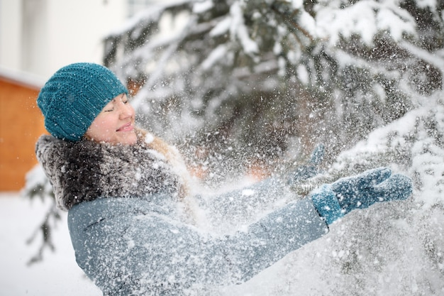 Woman during winter playing with snow