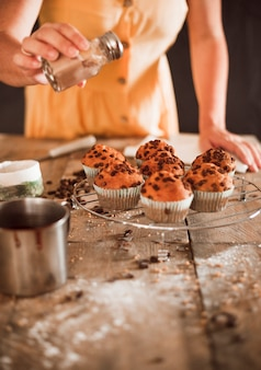 A woman dusting cocoa powder on homemade muffins on cooling rack