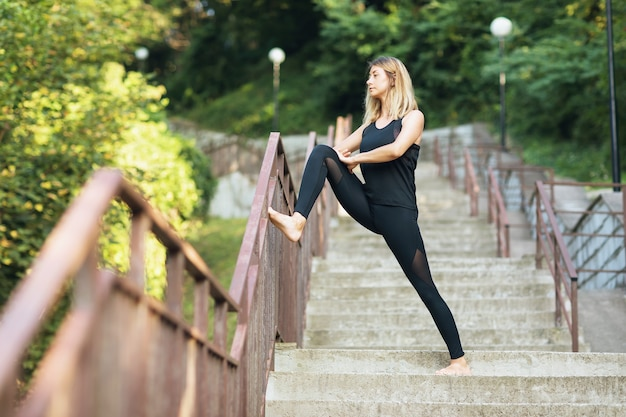 Woman in the early morning in the park performs an exercise to stretch the muscles of the legs