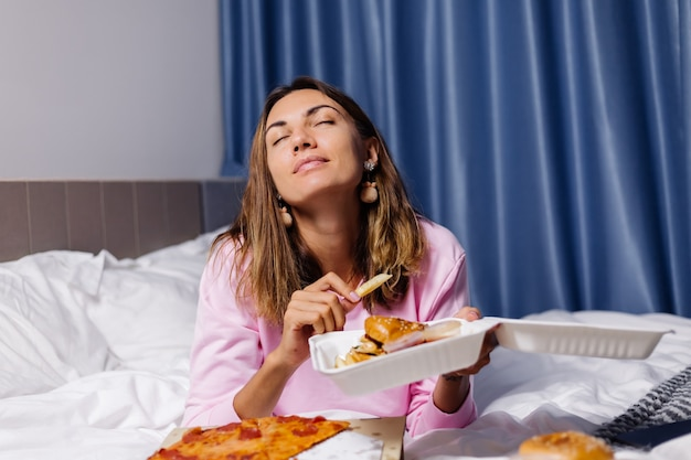 Woman east fast food from delivery on bed in bedroom at home female enjoying fat food pizza and burgers hungry for carbs