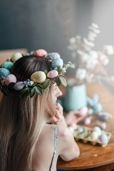 Woman in easter wreath at the table with easter eggs