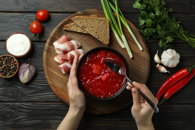 Woman eat borscht on wooden table with ingredients
