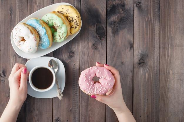 女性はドーナツを食べ、コーヒーを飲む