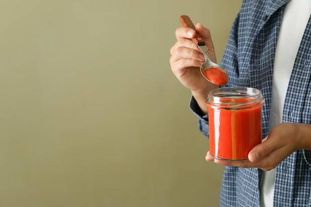 Woman eat gazpacho soup from glass jar