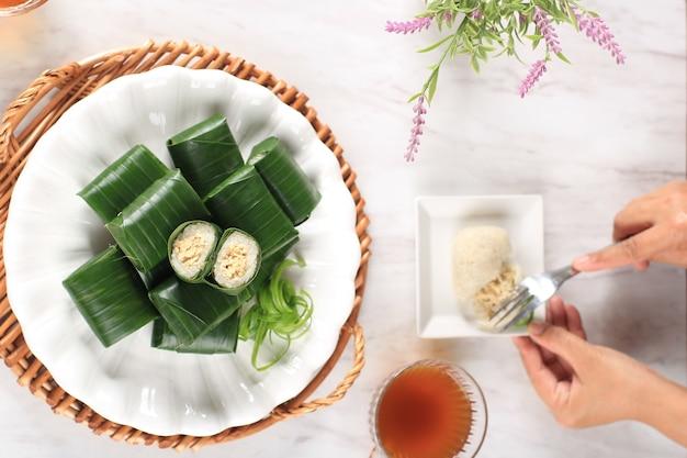 Женщина ест lemper вилкой. лемпер - это традиционное индонезийское блюдо из клейкого или липкого риса, приготовленное на пару с кокосовым молоком, с куриной нитью внутри и завернутое в цилиндрическую оболочку из банановых листьев.