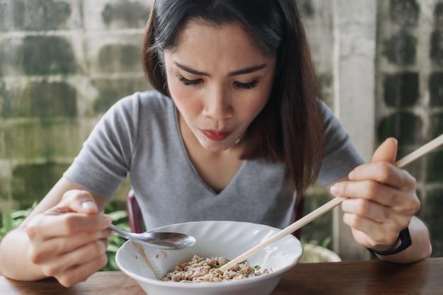 Женщина ест острую лапшу палочками для еды на местной улице