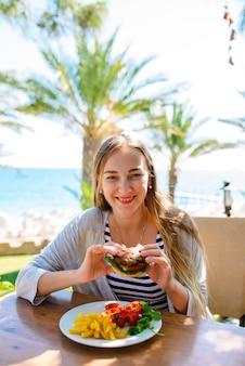 Женщина ест гамбургер и картофель фри на море