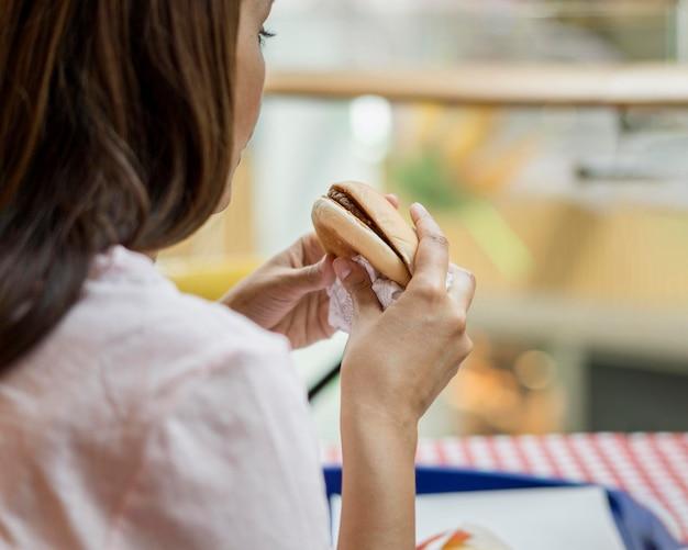 レストランでハンバーガーを食べる女性