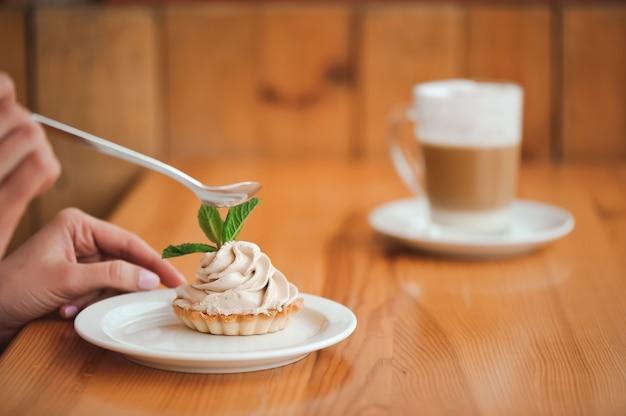 木製のテーブルのスプーンでセラミックプレートにカッテージチーズのケーキを食べる女。