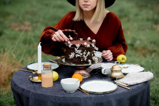 정원에서 초콜릿 케이크를 먹는 여자