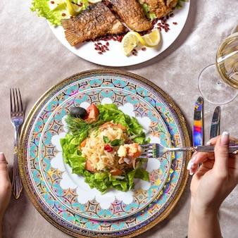 魚のサラダを食べる女性上面図