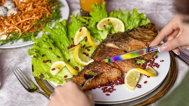 焼き魚をレモンと一緒に食べる女性