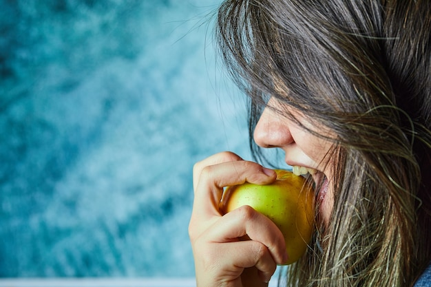 Woman eating apple on blue wall.