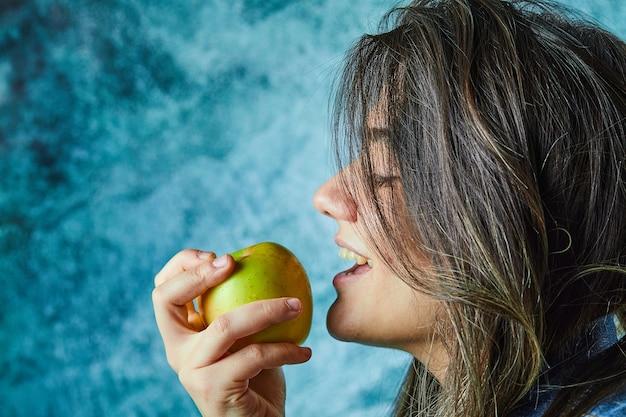 青い壁にリンゴを食べる女性。