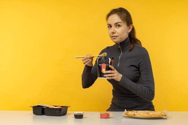 箸を使って鍋に野菜とアジアの中華料理麺を食べる女性。食品デリバリー。昼食を取りなさい。