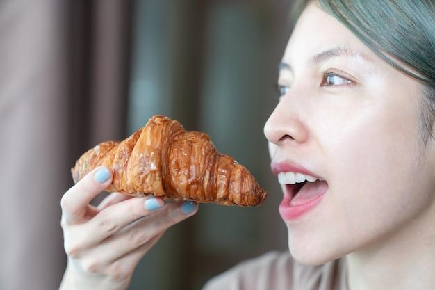 焼きたてのサクサククロワッサンを食べる女性。