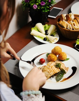 Woman eating baked salmon fillet with potatoes and cheese rolls, and vegetables mix.