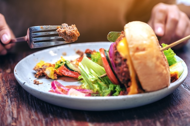 Woman eating beef hamburger with knife and fork in the restaurant