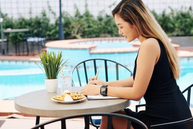 朝食を食べて日記を記入する女性
